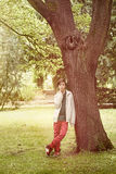Teenage boy leaning against a tree Stock Images