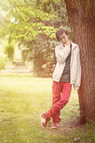 Teenage boy leaning against a tree Royalty Free Stock Photo