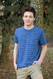 Teenage boy. Leaning pose against tree royalty free stock images