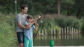 Teenage boy learning to fish with father`s help stock video