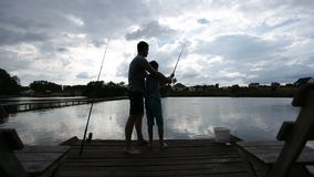 Teenage boy learning to fish with fishing rod stock footage