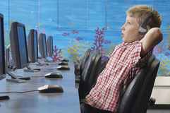Teenage Boy Listening Music In Lab. Side view of a relaxed young boy listening music in computer lab Royalty Free Stock Image