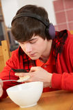 Teenage Boy Listening To MP3 Player Whilst Eating Stock Photo