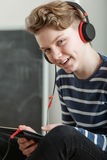 Teenage Boy Listening to Music Through Headphones Royalty Free Stock Images
