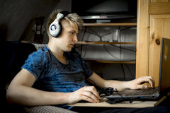 Teenage boy listening to music on his laptop. Teenage boy listening to music on stereo earphones attached to his laptop as he relaxes at a table indoors in his stock images