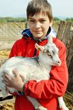 Teenage boy with little goat Royalty Free Stock Image