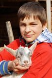 Teenage boy with little goat Royalty Free Stock Photo