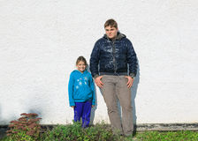 Teenage boy and little joyful happy girl standing against stucco old exterior house wall lighted by bright sunshine. Urban styled serious teenage boy and little Royalty Free Stock Photos