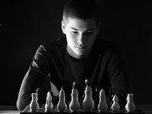 Teenage boy looking at the chessboard. Black and white photo Stock Image