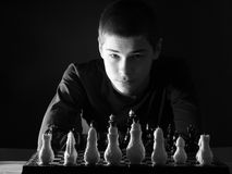 Teenage boy looking at the chessboard. Black and white photo Stock Images