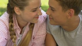 Teenage boy looking with love at girlfriend, nuzzling, adolescent pure love. Stock footage stock video