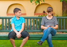Teenage boy looking with love at indifferent girl Stock Photo