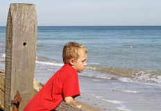 Teenage boy looking out the sea. Teenage boy looking out to sea at the beach Royalty Free Stock Image