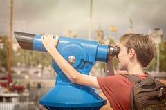 Teenage boy looking through a sightseeing monocula Stock Photos