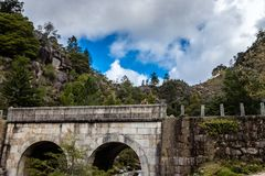 Teenage boy looks at bridge. Small mountain bridge over a creek from the Peneda Geres National Park, north of Portugal.  stock photography