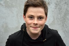 Teenage boy in black hoodie. Teenage boy with a lot of freckles, dressed with black hoodie sweater stock photography