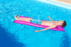Teenage boy lying on air mattress in swimming pool Royalty Free Stock Photo
