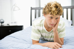 Teenage Boy Lying On Bed Stock Image