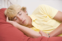 Teenage Boy Lying On Bed Royalty Free Stock Images