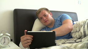 Teenage Boy Lying In Bed Using Digital Tablet Stock Photos