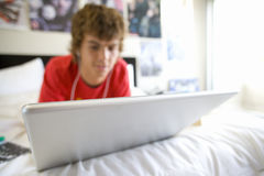 Teenage boy (16-18) lying on bed using laptop Stock Image