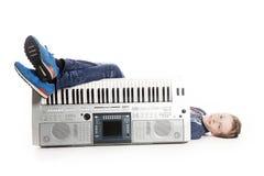 Teenage boy lying behind keyboard in studio Royalty Free Stock Photography