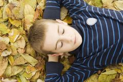 Teenage boy lying down with leaves around. Royalty Free Stock Image