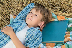 Teenage boy lying and dreaming inspired by book Stock Photography