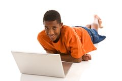 Teenage boy lying on front with laptop Royalty Free Stock Photography