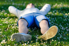 Teenage boy lying on meadow on sunny spring day Stock Image