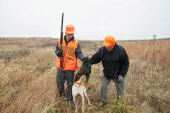 Teenage Boy and man pheasant hunting with German Shorthair dog. Teenage boy and grandfather grab pheasant retrieved from German Shorthair bird dog royalty free stock images