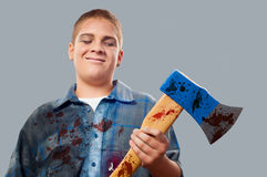 Teenage boy masked for halloween holding huge ax. Teenage boy masked for halloween holding huge bloody ax and smiling  on gray Stock Images