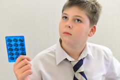 Teenage boy with the medicine in his hands Royalty Free Stock Photo