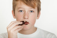 Teenage Boy with Messy Face Eating Chocolate Royalty Free Stock Photos