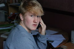 Teenage boy on mobile phone. Portrait teenage boy on mobile phone in home office Stock Photography