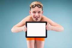 Teenage boy in orange shorts and swimming glasses hold empty tablet. Isolated on grey, teenage blond caucasian boy in orange shorts and swimming glasses, bend to Royalty Free Stock Photography