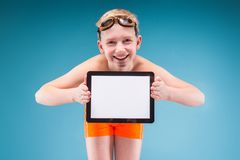 Teenage boy in orange shorts and swimming glasses hold empty tablet. Isolated on grey, teenage blond caucasian boy in orange shorts and swimming glasses, bend to Stock Photography