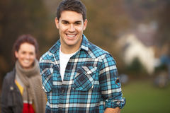 Teenage Boy Outside With Girlfriend In Background. Smiling at camera Stock Photography