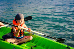 A teenage boy paddling a kayak on a lake. There is a fishing pole in the kayak with him. Royalty Free Stock Photo