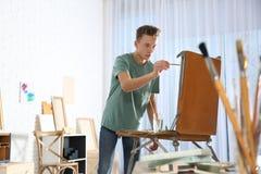 Teenage boy painting on easel in workshop. Hobby club royalty free stock photo
