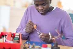 Teenage Boy Painting War Game Model Figures At Home. Teenage Boy Paints War Game Model Figures At Home royalty free stock photos