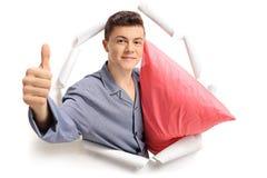 Teenage boy in pajamas breaking through paper and making a thumb. Teenage boy in pajamas with a pillow breaking through paper and making a thumb up sign Royalty Free Stock Photo