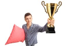 Teenage boy in pajamas holding a pillow and a golden trophy Royalty Free Stock Images
