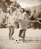 Teenage boy with parents playing in soccer Stock Images