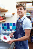 Teenage Boy With Part Time Job Washing Up In Coffee Shop Stock Photography
