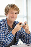 Teenage boy with phone in class Stock Photos