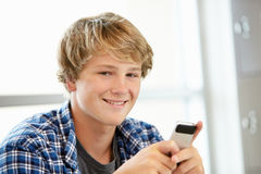 Teenage boy with phone in class Royalty Free Stock Images