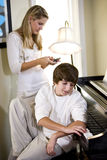 Teenage boy by piano with sister texting Royalty Free Stock Photo