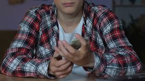 Teenage boy in plaid shirt counting money, sitting home table, financial savings stock video