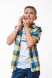 Teenage boy in a plaid shirt with a phone in his hand royalty free stock photography